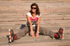 el Muchacha-rodillo se sienta en las escaleras Foto de archivo libre de regalías