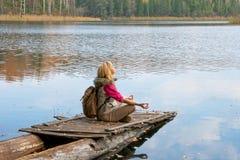 El muchacha-viajero en el embarcadero de madera viejo Fotos de archivo libres de regalías