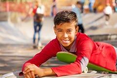 El muchacho árabe feliz en camisa roja pone en el monopatín Fotografía de archivo