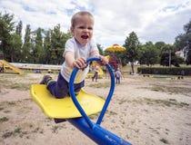 El muchacho 1 3 años de montar a caballo de la diversión en oscilaciones Foto de archivo libre de regalías