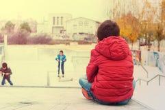 El muchacho 5 años que miran a los niños monta, juega Imagen de archivo