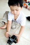 El muchacho absorbe en su pequeño coche del juguete Imagen de archivo