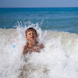El muchacho adentro salpica del mar Foto de archivo libre de regalías