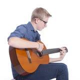 El muchacho adolescente caucásico en azul lleva los vidrios y juega el clásico Fotografía de archivo