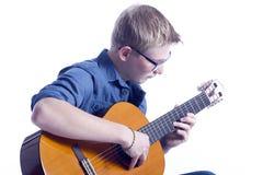 El muchacho adolescente caucásico en azul lleva los vidrios y juega el clásico Foto de archivo libre de regalías