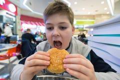 El muchacho adolescente come el café de la hamburguesa n Foto de archivo libre de regalías