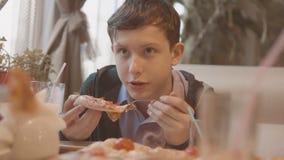El muchacho adolescente come la pizza en vídeo de la cámara lenta del café él sirve está comiendo una pizza deliciosa compañía de metrajes