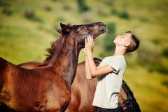 El muchacho adolescente comunica con los caballos Foto de archivo libre de regalías