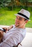 El muchacho adolescente con el sombrero blanco se relaja en el jardín Imagenes de archivo
