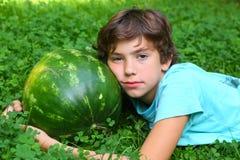 El muchacho adolescente con la sandía entera pone en hierba verde Imagen de archivo
