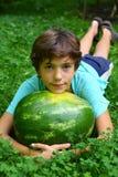 El muchacho adolescente con la sandía entera pone en hierba verde Foto de archivo libre de regalías