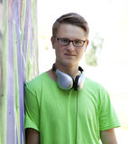 El muchacho adolescente con los auriculares acerca a la pared de la pintada. Imagen de archivo