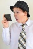 El muchacho adolescente con sorpresa mira el teléfono móvil Fotos de archivo