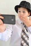 El muchacho adolescente con sorpresa mira el teléfono móvil Imagen de archivo libre de regalías