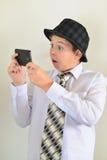 El muchacho adolescente con sorpresa mira el teléfono móvil Fotografía de archivo