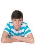 El muchacho adolescente confiado está mintiendo en el blanco Fotos de archivo