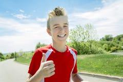 El muchacho adolescente corre afuera en una luz del día Foto de archivo