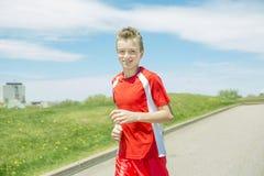El muchacho adolescente corre afuera en una luz del día Imágenes de archivo libres de regalías