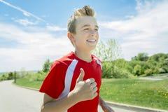 El muchacho adolescente corre afuera en una luz del día Foto de archivo libre de regalías