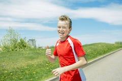 El muchacho adolescente corre afuera en una luz del día Fotos de archivo libres de regalías