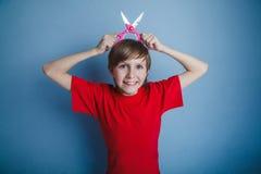 El muchacho, adolescente, doce años en camisa roja bebe Imágenes de archivo libres de regalías