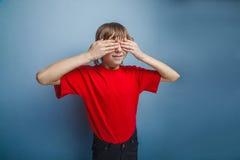 El muchacho, adolescente, doce años en camiseta roja, observa Foto de archivo libre de regalías