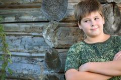 El muchacho adolescente en camuflaje se coloca cerca de la pared de madera Imagenes de archivo