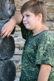 El muchacho adolescente en camuflaje se coloca cerca de la pared de madera Foto de archivo libre de regalías