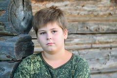 El muchacho adolescente en camuflaje se coloca cerca de la pared de madera Fotos de archivo