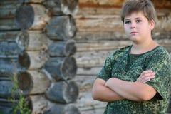 El muchacho adolescente en camuflaje se coloca cerca de la pared de madera Fotografía de archivo libre de regalías