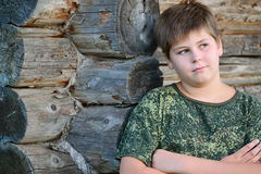 El muchacho adolescente en camuflaje se coloca cerca de la pared de madera Imagen de archivo