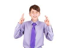 El muchacho adolescente en una camisa y un lazo que guardaban los brazos cruzó aislado en blanco Fotos de archivo