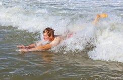 El muchacho adolescente es carrocería que practica surf en el océano Imagenes de archivo