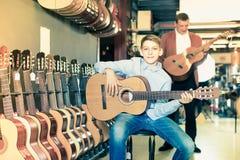 El muchacho adolescente es orgulloso comprar una nueva guitarra Foto de archivo