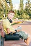 El muchacho adolescente es que se sienta y de escritura en el banco Foto de archivo