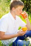 El muchacho adolescente es vidrio de consumición con el zumo de naranja Foto de archivo