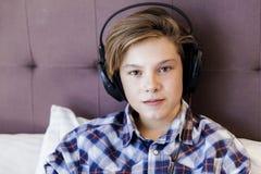 El muchacho adolescente escucha música en cama Foto de archivo libre de regalías