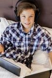 El muchacho adolescente escucha música en cama Imágenes de archivo libres de regalías
