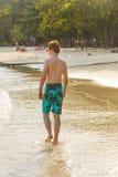 El muchacho adolescente está caminando a lo largo de la playa tropical Imagen de archivo