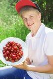 El muchacho adolescente está llevando el casquillo rojo que sostiene las fresas Fotografía de archivo