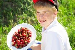 El muchacho adolescente está llevando el casquillo rojo que sostiene las fresas Imagen de archivo libre de regalías