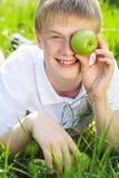 El muchacho adolescente está sosteniendo la manzana verde cerca de cara Imágenes de archivo libres de regalías