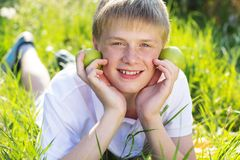 El muchacho adolescente está sosteniendo manzanas verdes Imagen de archivo