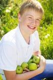El muchacho adolescente está sosteniendo manzanas verdes Foto de archivo libre de regalías