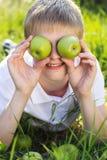 El muchacho adolescente está sosteniendo manzanas verdes Fotografía de archivo libre de regalías