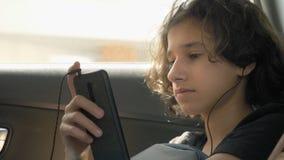 El muchacho adolescente feliz en auriculares utiliza el teléfono en coche almacen de metraje de vídeo