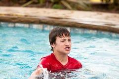 El muchacho adolescente feliz en piscina con los labios frunció Imagenes de archivo