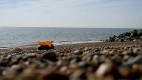 El muchacho adolescente flota en la playa británica en el colchón inflable almacen de metraje de vídeo