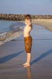 El muchacho adolescente goza de la playa en sol de la mañana Imágenes de archivo libres de regalías