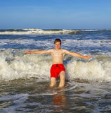 El muchacho adolescente goza de las ondas en el océano áspero Foto de archivo libre de regalías